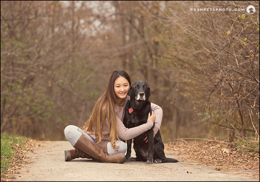 girl hugging dog in a forest