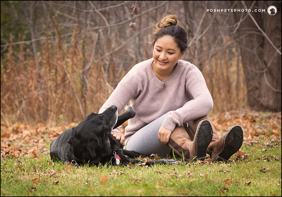 dog rolling on grass with girl