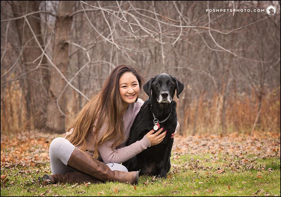 girl hugging black labrador dog